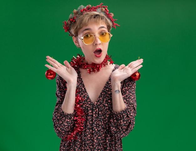 Jovem bonita impressionada com a coroa da cabeça de natal e guirlanda de ouropel no pescoço, com óculos segurando enfeites de natal olhando para a câmera