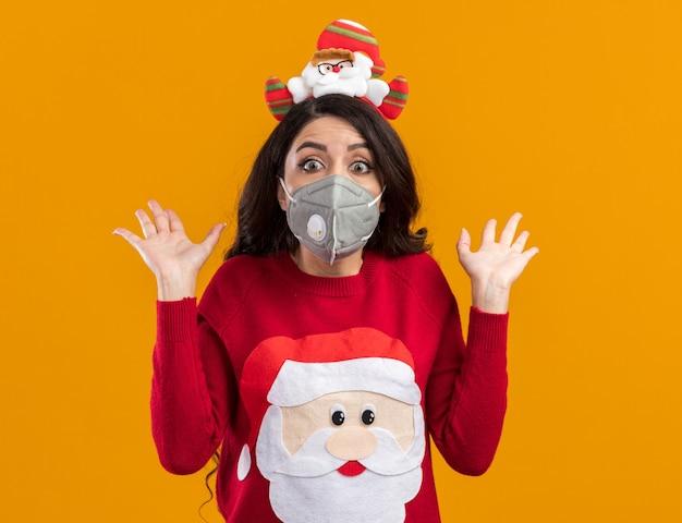 Jovem bonita impressionada com bandana de papai noel e suéter com máscara protetora mostrando as mãos vazias isoladas na parede laranja