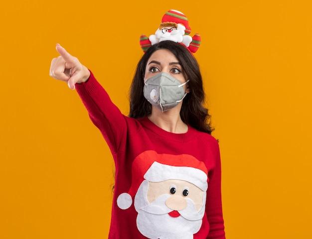 Jovem bonita impressionada com bandana de papai noel e suéter com máscara protetora olhando e apontando para o lado