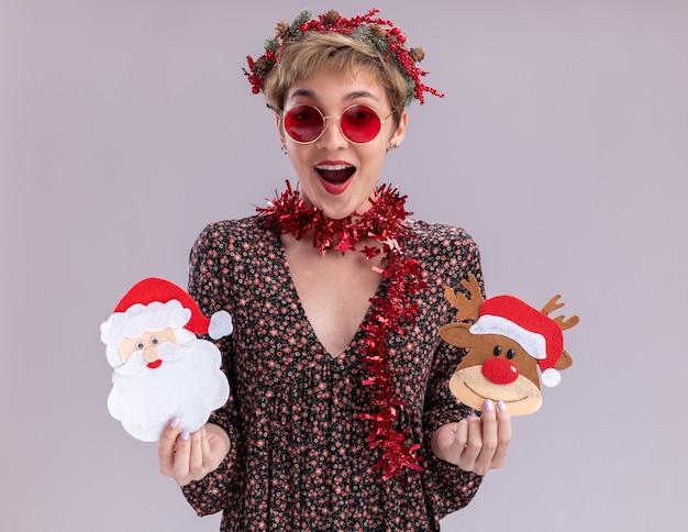 Jovem bonita impressionada com coroa de flores de natal e guirlanda de ouropel em volta do pescoço com óculos segurando renas de natal e enfeites de papel de papai noel isolados na parede branca