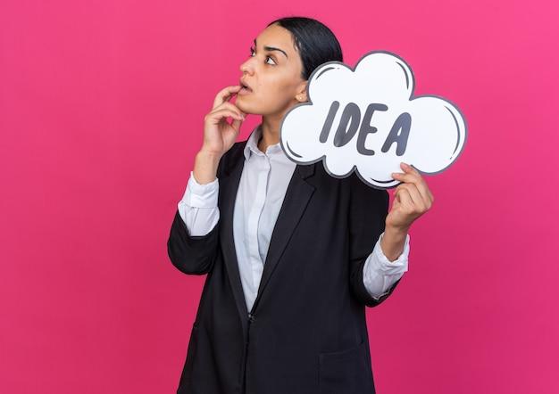 Jovem bonita impressionada com um blazer preto segurando um balão de ideia e colocando a mão na boca