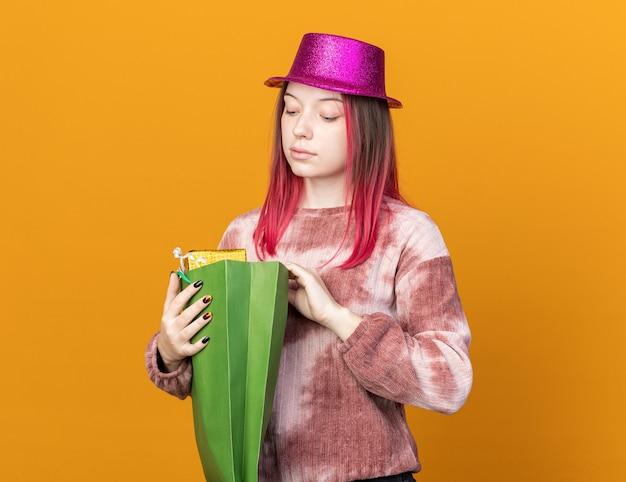 Jovem bonita impressionada com um chapéu de festa segurando e olhando para uma sacola de presente isolada na parede laranja
