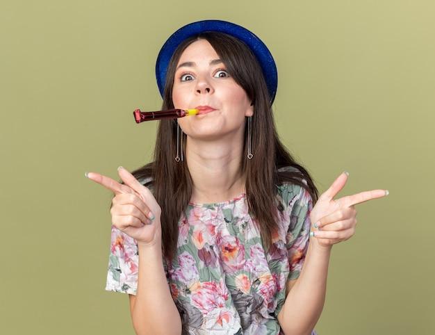 Jovem bonita impressionada com um chapéu de festa soprando apitos de festa nas laterais isoladas em uma parede verde oliva