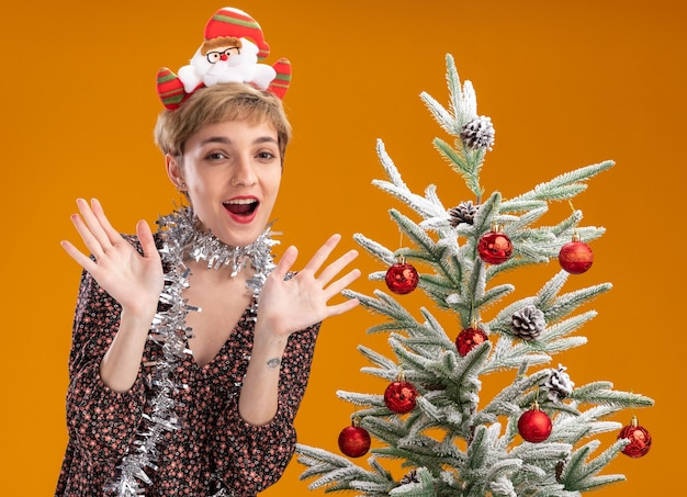 Jovem bonita impressionada com uma faixa de papai noel e guirlanda de ouropel no pescoço, em pé perto da árvore de natal decorada, mostrando as mãos vazias isoladas na parede laranja