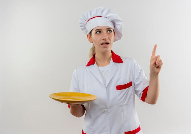 Jovem bonita impressionada com uniforme de chef segurando o prato vazio olhando e apontando para cima, isolado na parede branca