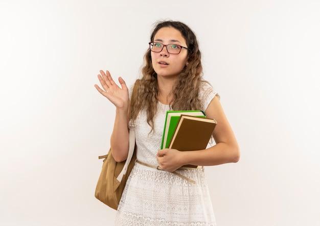 Jovem bonita impressionada de colegial de óculos e bolsa traseira segurando livros, mostrando a mão vazia olhando para cima isolado no branco