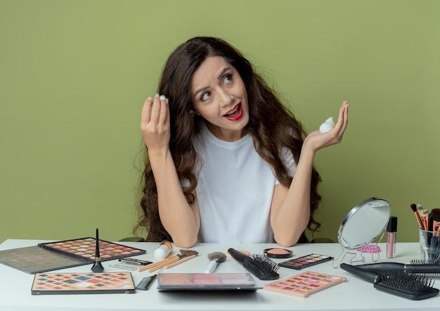 Jovem bonita impressionada sentada à mesa de maquiagem com ferramentas de maquiagem, aplicando mousse de cabelo no cabelo e olhando para o lado isolado no fundo verde oliva