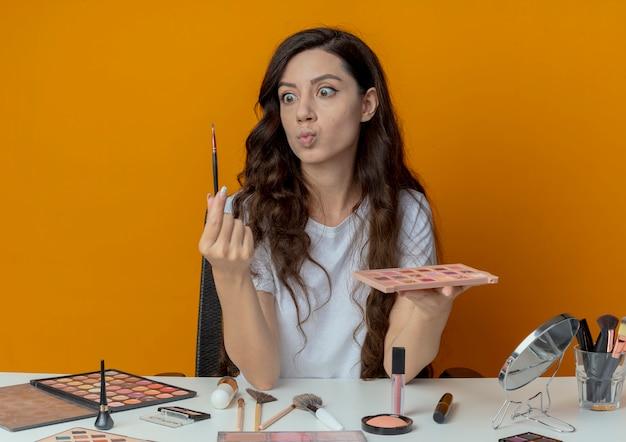 Jovem bonita impressionada sentada à mesa de maquiagem com ferramentas de maquiagem segurando a paleta de sombra e o pincel e olhando para o pincel isolado em um fundo laranja