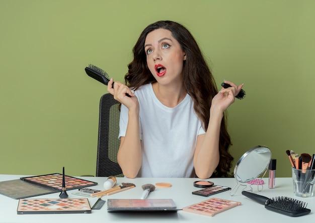 Jovem bonita impressionada sentada à mesa de maquiagem com ferramentas de maquiagem segurando pentes, olhando para cima isoladas em fundo verde oliva