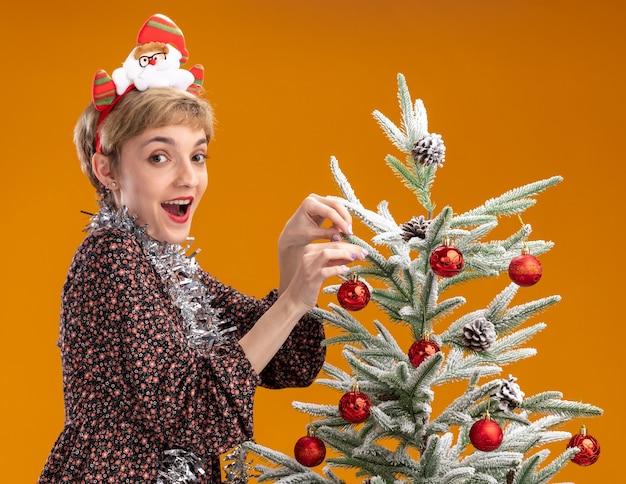 Jovem bonita impressionada usando bandana de papai noel e guirlanda de ouropel em volta do pescoço em pé na vista de perfil perto da árvore de natal decorando-a com enfeites de natal isolados na parede laranja