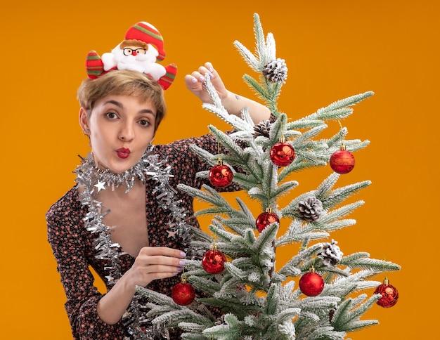 Jovem bonita impressionada usando bandana de papai noel e guirlanda de ouropel no pescoço em pé atrás da árvore de natal decorada tocando-a fazendo gesto de beijo isolado na parede laranja
