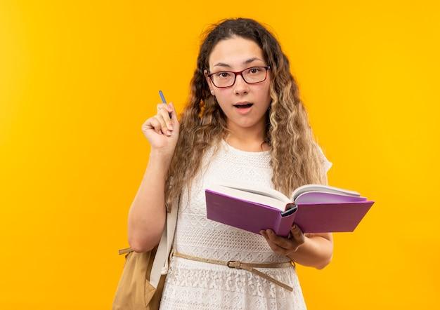 Jovem bonita impressionada usando óculos e bolsa traseira segurando caneta e livro isolado no amarelo