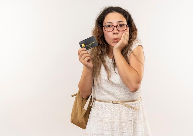 Jovem bonita impressionada usando óculos e bolsa traseira segurando um cartão de crédito com a mão no rosto isolado no branco