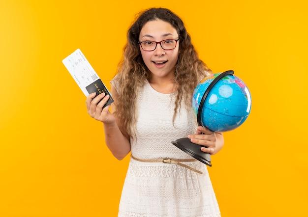 Jovem bonita impressionada usando óculos, segurando uma passagem de avião, um cartão de crédito e um globo isolado em amarelo