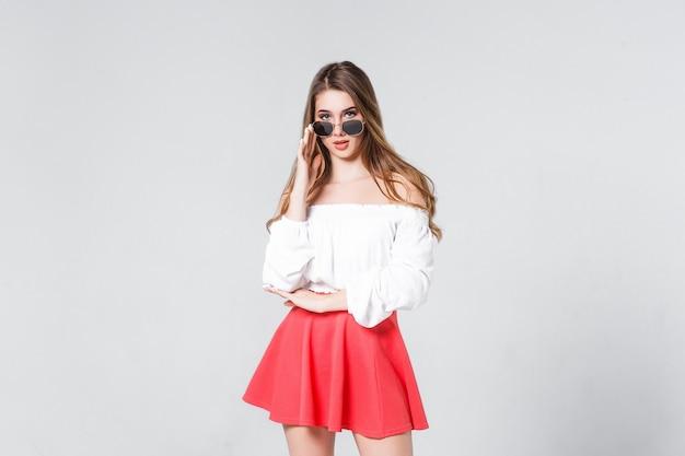 Jovem bonita, incrível, com longos cabelos loiros encaracolados, em saia rosa, em óculos de sol cinza, brancos, ficando em branco.