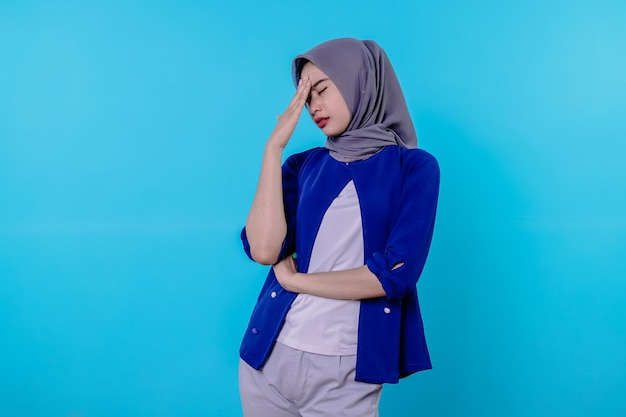 Jovem bonita latina olhando concentrada e pensando seriamente em uma ideia, imaginando uma solução para um desafio ou problema contra a parede azul