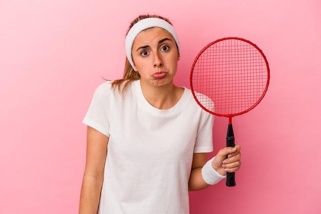 Jovem bonita loira caucasiana mulher segurando uma raquete de badminton isolada no fundo rosa encolhe os ombros e abre os olhos confusos.