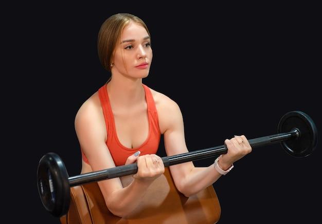 Jovem bonita loira desportiva segurando uma barra na academia em fundo preto