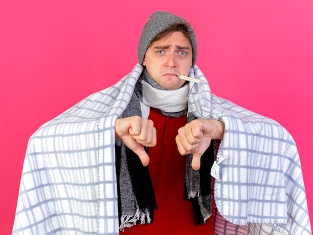 Jovem bonita loira doente, descontente, usando chapéu de inverno e cachecol embrulhado em xadrez segurando o termômetro na boca, mostrando os polegares para baixo, olhando para frente, isolado na parede rosa