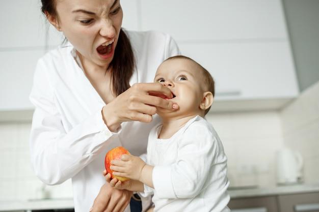 Jovem bonita mãe alimentando com pêssego seu filho pequeno na cozinha. mãe fazendo uma expressão engraçada para fazer seu filho rir.