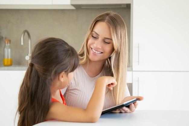 Jovem bonita mãe e filha usando tablet e sorrindo um ao outro.