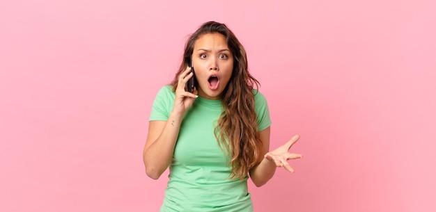 Jovem bonita maravilhada, chocada e atônita com uma surpresa inacreditável e segurando um telefone inteligente