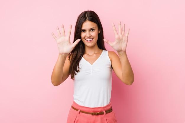 Jovem bonita mostrando o número dez com as mãos.