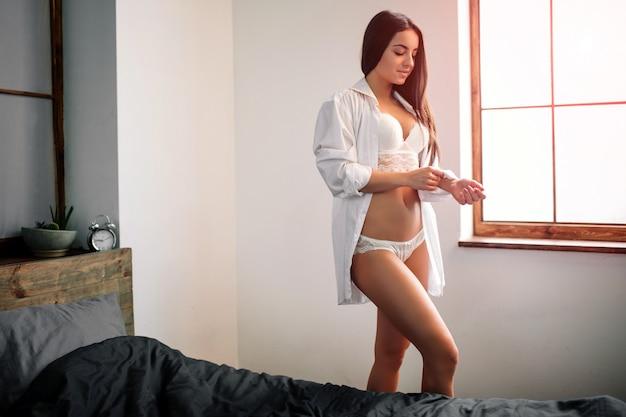 Jovem bonita, mulher acordando de manhã totalmente descansada.