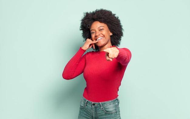 Jovem bonita negra fazendo gesto de telefone com a mão, me ligue