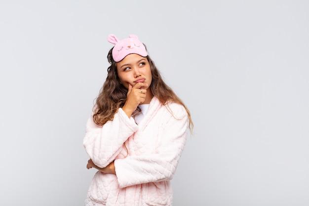 Jovem bonita pensando, sentindo-se duvidosa e confusa, com diferentes opções, imaginando qual decisão tomar de pijama