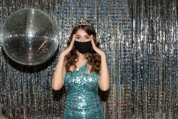 Jovem bonita pensativa com vestido brilhante com lantejoulas e coroa em máscara médica preta na festa