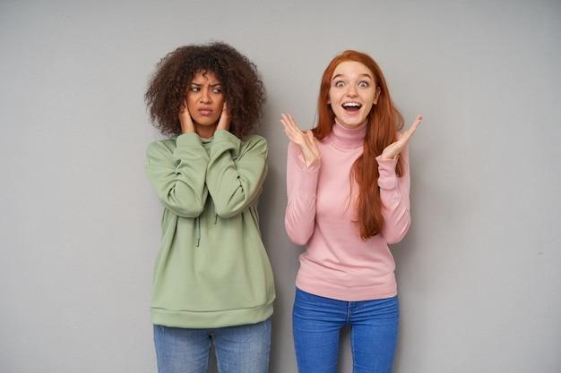 Jovem bonita ruiva animada levantando as mãos e olhando maravilhada enquanto posava sobre uma parede cinza com uma mulher séria de cabelos castanhos e pele escura descontente