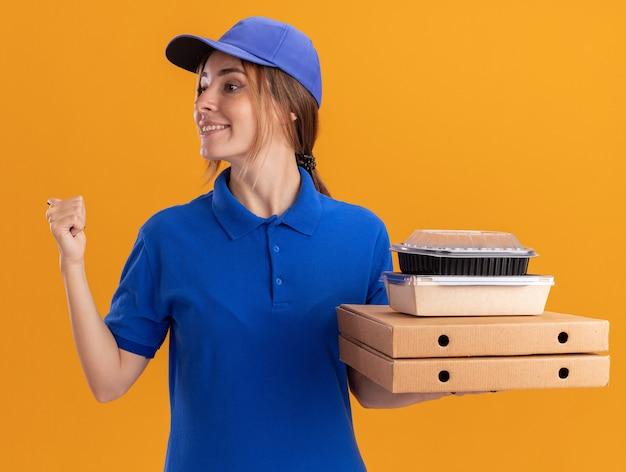 Jovem, bonita, satisfeita, entregadora de uniforme aponta para trás e segura embalagens de papel e embalagens de comida em caixas de pizza, olhando para o lado laranja