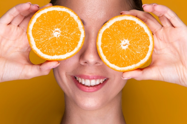 Jovem bonita segurando fatias de laranja
