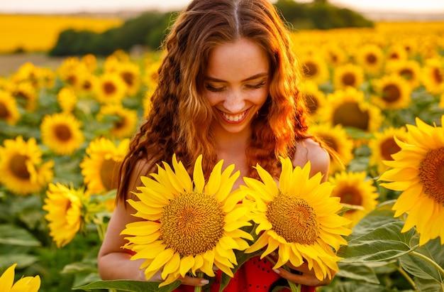 Jovem bonita segurando girassol na mão enquanto está no campo ao pôr do sol