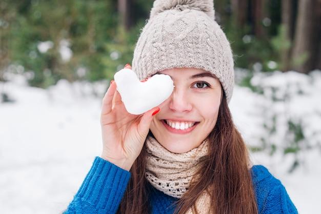 Jovem bonita, segurando o coração de neve na floresta de inverno. conceito de amor dia dos namorados.
