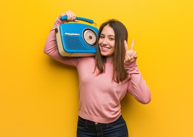 Jovem bonita, segurando um rádio vintage, mostrando o número dois