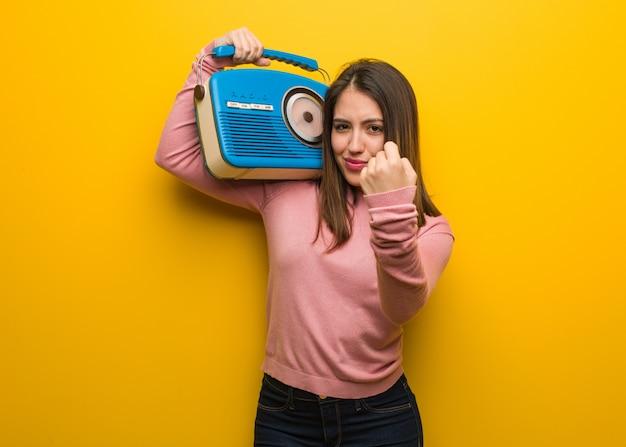 Jovem bonita, segurando um rádio vintage, mostrando o punho para a frente, expressão de raiva