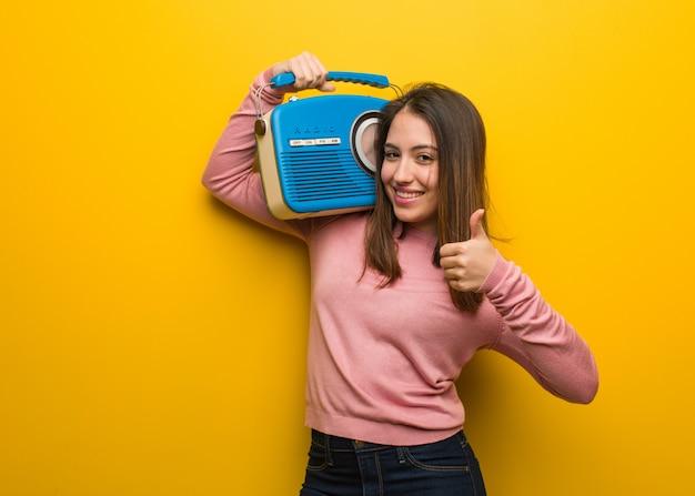Jovem bonita, segurando um rádio vintage, sorrindo e levantando o polegar