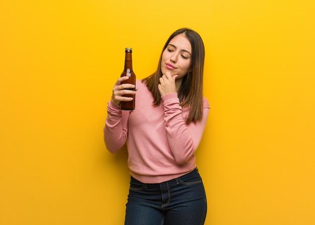 Jovem bonita, segurando uma cerveja duvidosa e confusa