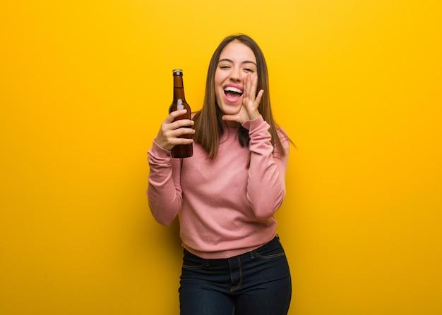 Jovem bonita, segurando uma cerveja gritando algo feliz para a frente