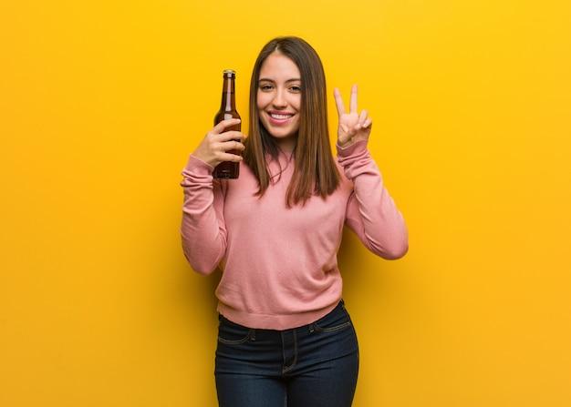 Jovem bonita, segurando uma cerveja, mostrando o número dois