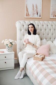 Jovem bonita senta-se em uma cama grande com uma caixa de marshmallows