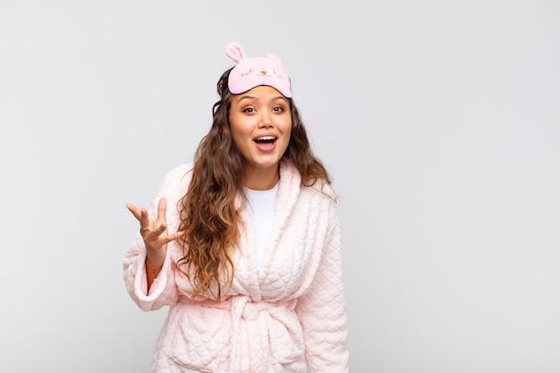 Jovem bonita sentindo-se feliz, surpresa e alegre, sorrindo com atitude positiva, percebendo uma solução ou ideia de pijama