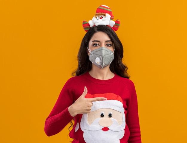 Jovem bonita séria com bandana de papai noel e suéter com máscara protetora apontando para o lado isolado na parede laranja