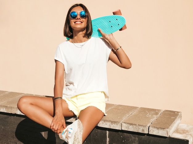 Jovem bonita sexy sorridente mulher hipster em óculos de sol. garota na moda em t-shirt e shorts de verão. mulher positiva com centavo azul skate posando no fundo da rua