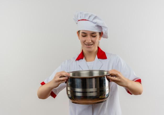 Jovem bonita sorridente com uniforme de chef e aparelho dentário segurando e olhando para a panela isolada no espaço em branco