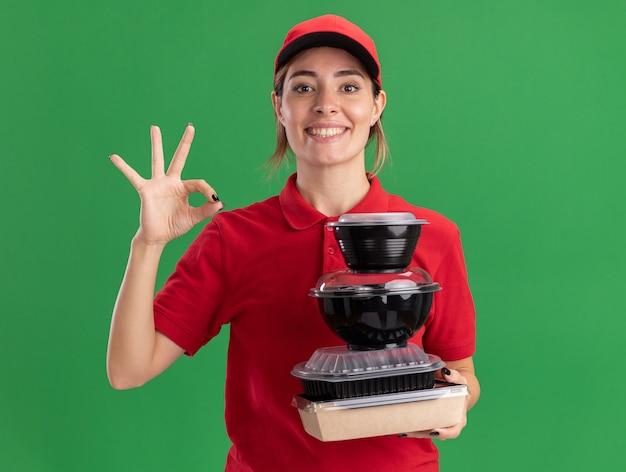 Jovem bonita sorridente, entregadora de uniforme, gesticula com a mão bem sinalizada e segura os recipientes de comida no pacote de comida no verde