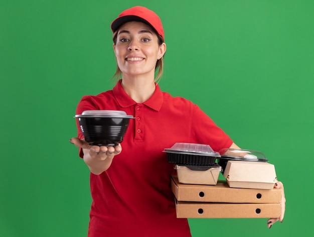 Jovem bonita sorridente, entregadora de uniforme, segurando pacotes de comida de papel em caixas de pizza e recipientes de comida em verde