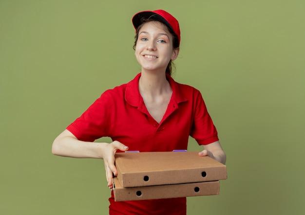 Jovem bonita sorridente, entregadora de uniforme vermelho e boné segurando pacotes de pizza